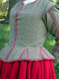 The sleeves are sewn into the armescye with a backstitch, the excess turned down and a sleeve lining of unbleached linen stitched over the raw edges. Seam allowances in garments of the time were narrower than they are today; 1/4 to 3/8 of an inch was common.