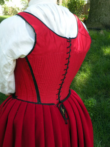 This petticoat laced closed at the back. The pleats are knife pleats, with a layer of wool pleated in with the outer fabric. The waistband is bound around the raw edges of the pleats.
