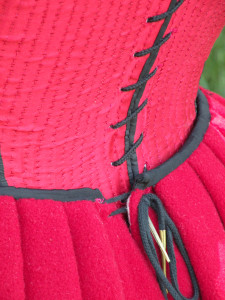 point laces through two holes on either side of the petticoat's back opening. This allows for considerable adjustability. Also, when the laces are tied together after being threaded through both sets of holes, they stay laced remarkably well--it takes work to loosen the hitch.