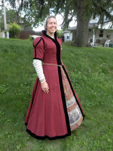 The gown is russet wool lined with brown linen. It hooks up the front with hooks and eyes.